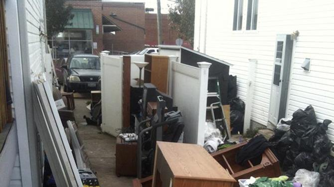 """This Nov. 1, 2012, photo taken from Facebook shows a broken fence and a number of items belonging to Associated Press sports writer Dennis Waszak Jr., and his family that were cleaned out of the basement after their """"dream house"""" was damaged by Superstorm Sandy in the Staten Island borough of New York. (AP Photo)"""