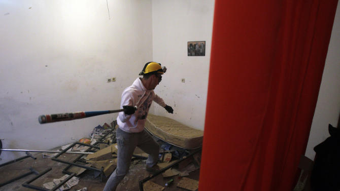 In this Dec. 27, 2012 photo visitor Savo Duvnjak smashes furniture and other household items during a demolishing session at the Rage Room, in Novi Sad, Serbia. Since it opened in the northern Serbian city of Novi Sad in October, Serbia's Rage Room has drawn much publicity in the Balkan country where two decades or wars, crisis and economic hardship have driven many over the edge. Inspired by a similar Anger Room business in Dallas, Texas, Serbia's version was set up by two teens who saw the U.S. room idea on the Internet and figured it could be a good way to earn pocket money. (AP Photo/Darko Vojinovic)