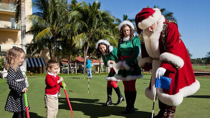 IMAGE DISTRIBUTED FOR MACY'S - Carina Ballard, 6, left and her brother, Blake, 3, play golf with Santa Claus and his elves during the Macy's National Santa Tour at the The Ritz Carlton Golf Resort in Naples, Fla., Friday, Dec. 21, 2012. Santa made the stop at the resort to play golf with 10 Make-A-Wish children and their families as part of the Macy's national tour. (Erik Kellar/AP Images for Macy's)