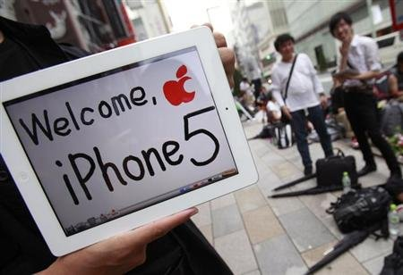 People wait in line to buy Apple Inc's iPhone 5 as an Apple fan shows his iPad outside Apple Store in Tokyo's Ginza district September 21, 2012.