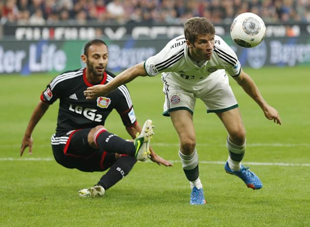 Leverkusen's Omer Toprak of Turkey, left, and Bayern's Thomas Mueller challenge for the ball during the German first division Bundesliga soccer match between Bayer Leverkusen and Bayern Munich in Leve