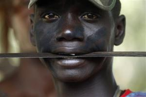 "A fighter from the Christian ""anti-balaka"" militia holds a machete in his mouth at the headquarters in the northern Bangui suburb of Boeing"