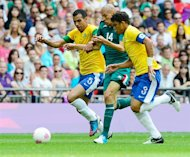 Mexico's midfielder Jorge Enriquez (C) vies for the ball with Brazil's midfielder Sandro (L) and Brazil's defender Thiago Silva (R) during the men's football final match between Brazil and Mexico at the Wembley stadium in London during the London Olympic Games on August 11, 2012. AFP PHOTO / DANIEL GARCIA