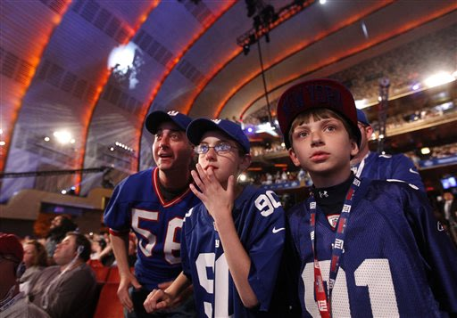 New York Giants fans, from left, Jeff Becker and his son Reed, 11, both of Livingston, N.J., and Nate Casharay, 10, of Cornwall, N.Y., wait for the announcement of the Giants' third round pick, the 81