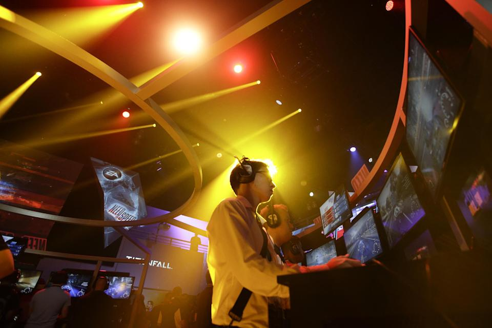 "Frank Cire, center, plays the ""Need for Speed"" racing video game at the EA booth during the Electronic Entertainment Expo in Los Angeles, Wednesday, June 12, 2013. (AP Photo/Jae C. Hong)"