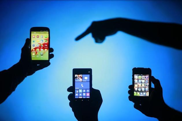Men are silhouetted against a video screen as they pose with Samsung Galaxy S3, Nokia Lumia 820 and iPhone 4 smartphones (L-R) in this photo illustration taken in the central Bosnian town of Zenica, May 17, 2013. REUTERS/Dado Ruvic