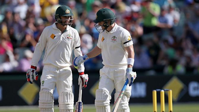 Australia's Peter Nevill, right, and batting partner Nathan Lyon meet mid-wicket during a change of ends while playing New Zealand in their cricket test in Adelaide, Saturday, Nov. 28, 2015. This match is the sport's first ever day-night test. (AP Photo/Rick Rycroft)