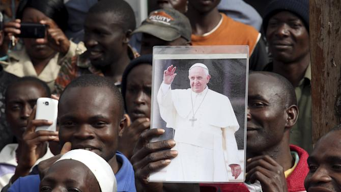 A faithful holds a Pope Francis picture at the Kangemi slums on the outskirt of Kenya's capital Nairobi