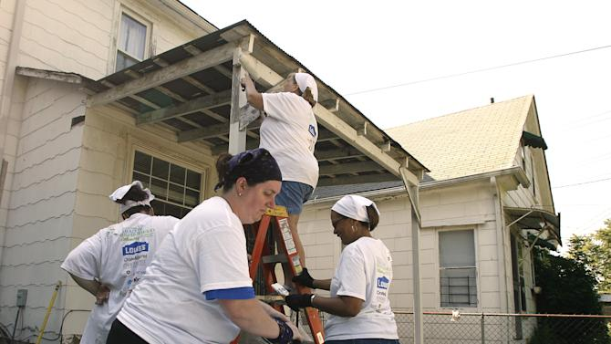 IMAGE DISTRIBUTED FOR REBUILDING TOGETHER - Bonnie Bessor paints plywood as she joined hundreds of volunteers participating in Rebuilding Together's Building a Healthy Neighborhood event on Friday, June 21, 2013 in the Hilltop neighborhood of Columbus, Ohio. Rebuilding Together is a national non-profit that provides critical home repairs and improvements to low-income homeowners in communities across America. (Mike Munden / AP Images for Rebuilding Together)