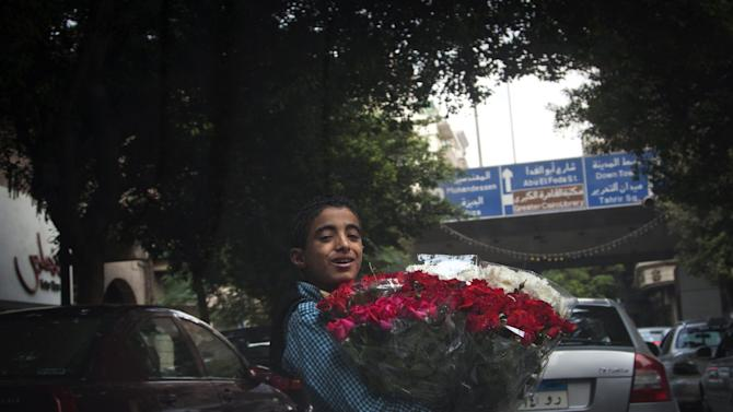 In this Oct. 24, 2012 photo, An Egyptian child sells flowers at a street in Cairo, Egypt. The Egyptian government estimates that some 1.6 million minors work - almost 10 percent of population aged 17 or under,  often in arduous conditions. Other experts put the number at nearly twice that. Some child labor activists worry that protections for children could be loosened further under the new constitution still being written. Earlier this month, the Egyptian Coalition for Children's Rights warned that early drafts of the document did not include as firm prohibitions on child labor as past constitutions.(AP Photo/Khalil Hamra)