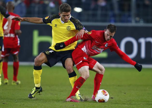 Freiburg's Vladimir Darida (R) challenges Sevilla's Daniel Carrico during their Europa League soccer match in Freiburg