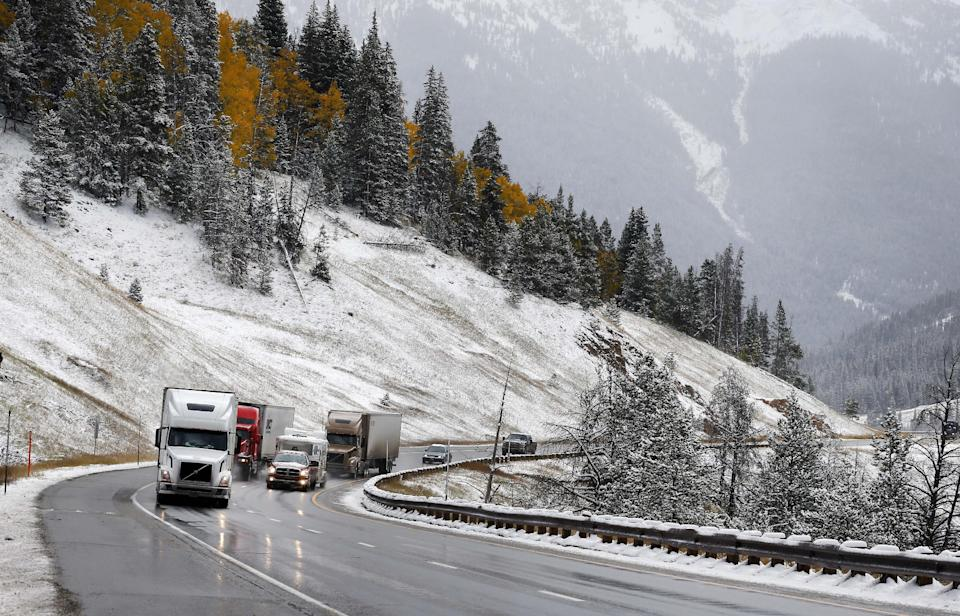 Trucks ascend Vail Pass along I-70 after overnight snow fell in the mountains of Colorado. Friday Oct. 4, 2013. Powerful storms moved into the Midwest on Friday due to a cold weather system gaining strength as it traveled east from Colorado and Wyoming. (AP Photo/Brennan Linsley)