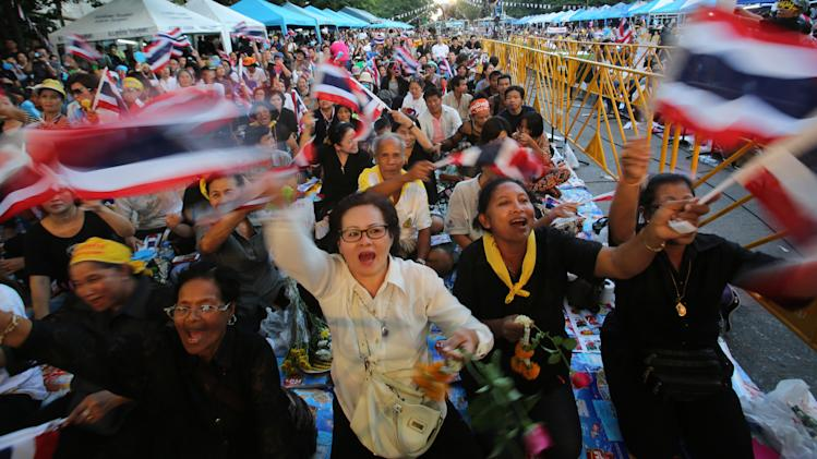 Anti-government protesters wave Thai national flags and chant slogans during a rally against the amnesty bill in Bangkok, Thailand, Friday, Nov. 1, 2013. Thai parliament on Friday moved a step closer to granting amnesty to people involved in a wrenching political conflict that has divided the country for almost a decade, prompting thousands to protest in the streets and renewing fears of violence. (AP Photo/Sakchai Lalit)