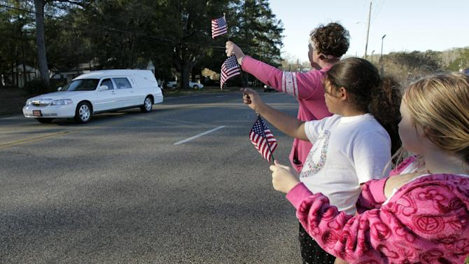 "Gabriel Cavender, right, Kiya Buchanan, center, and Raechel Buchanan, left, hold up flags as the funeral procession for Charles ""Chuck"" Poland passes by on Sunday, Feb. 3, 2013, in Ozark, Ala. (AP Photo/Butch Dill)"