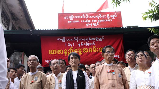 Myanmar democracy icon Aung San Suu Kyi, center, and members of her National League for Democracy party pay tribute to the independence heroes of Myanmar, during Martyr's Day ceremonies held outside the NLD headquarters Tuesday, July 19, 2011, in Yangon, Myanmar. (AP Photo/Khin Maung Win)