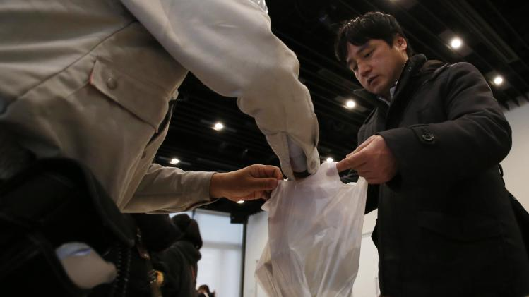 A participant, acting as a stranded pedestrian, receives emergency food at a shelter during an earthquake simulation exercise at Akihabara in Tokyo