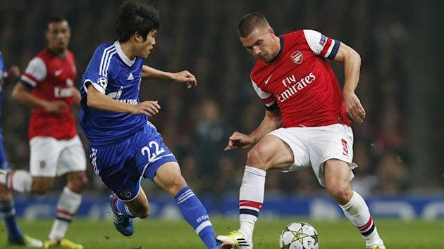 Arsenal's Lukas Podolski (R) is challenged by Schalke 04's Atsuto Uchida (Reuters)
