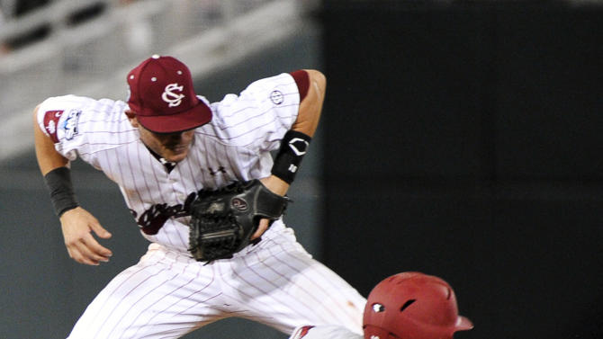 Arkansas' Bo Bigham (12) steals second base against South Carolina second baseman Chase Vergason on his way to third on a throwing error in the sixth inning of an NCAA College World Series baseball game in Omaha, Neb., Monday, June 18, 2012. (AP Photo/Ted Kirk)