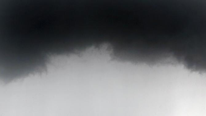 A Greek national flag and an EU flag flutter under storm clouds in Athens