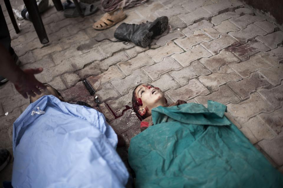 In this Thursday, Oct. 11, 2012 photo, the bodies of two Syrian children, killed by Syrian Army shelling, lie on the street near Dar al-Shifa hospital in Aleppo, Syria. (AP Photo/Manu Brabo)