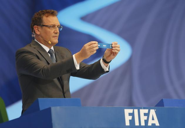 "Valcke holds up the slip showing ""Italy"" during the draw for the 2014 World Cup in Sao Joao da Mata"