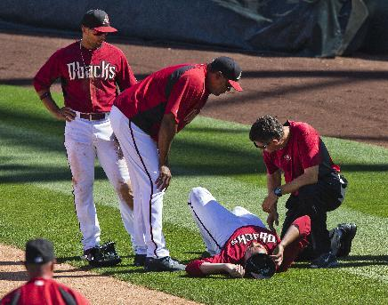 Arizona Diamondbacks pitcher Trevor Cahill lies on the field after jamming his knee covering first base, during an exhibition baseball game against the Cleveland Indians on Tuesday, March 11, 2014, in Scottsdale, Ariz