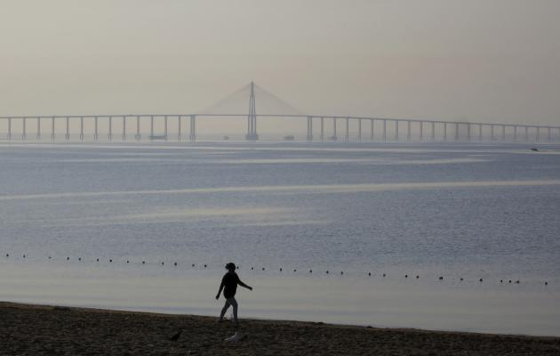 A woman walks along a beach next to the Amazon River at sunrise in Manaus, Brazil