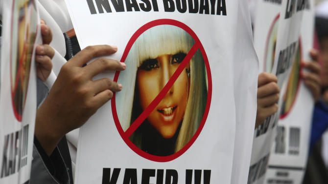 """A Muslim woman holds a poster bearing a defaced picture of U.S. pop singer Lady Gaga during a protest against her concert that is scheduled to be held on June 3, in Jakarta, Indonesia, Thursday, May 24, 2012. Lady Gaga might have to cancel her sold-out show in Indonesia because police worry her sexy clothes and dance moves undermine Islamic values and will corrupt the country's youth. The writing on the poster reads """"Infidel.""""  (AP Photo/Tatan Syuflana)"""