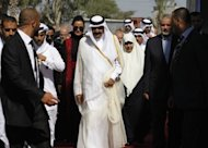 Surrounded by security guards, Qatari Emir Sheikh Hamad bin Khalifa al-Thani (C), his wife Qatar's First Lady Sheikha Mozah bint Nasser al-Missned (C), Gaza's Hamas prime minister Ismail Haniya (R) and his wife (3rdR), attend a welcome ceremony at the Rafah border crossing with Egypt in the Gaza Strip