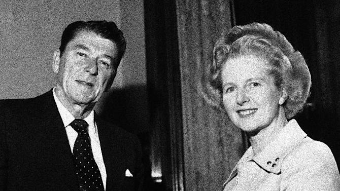 """FILE - In this April 9, 1975 file photo, former California Governor Ronald Reagan presents a silver dollar medallion to Opposition Leader Margaret Thatcher when he visited her office at the House of Commons in London.  Ex-spokesman Tim Bell says that Thatcher has died. She was 87. Bell said the woman known to friends and foes as """"the Iron Lady"""" passed away Monday morning, April 8, 2013. (AP Photo/File)"""