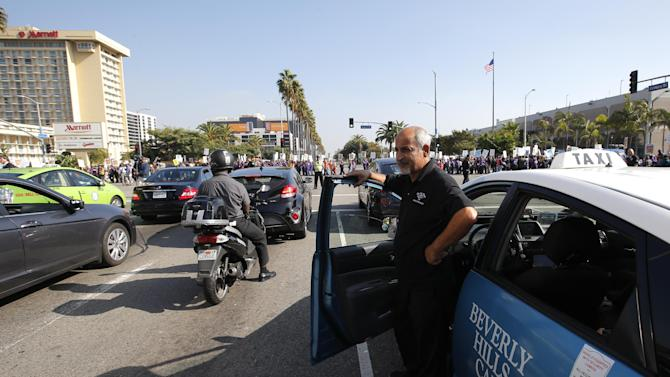A taxi driver watches as union workers at Los Angeles International Airport march along the street near the airport in Los Angeles, Wednesday, Nov. 21, 2012. Hundreds of union members marched Wednesday near the entrance to Los Angeles International Airport, where Thanksgiving travelers were warned to arrive early in case of traffic snarls. (AP Photo/Jae C. Hong)