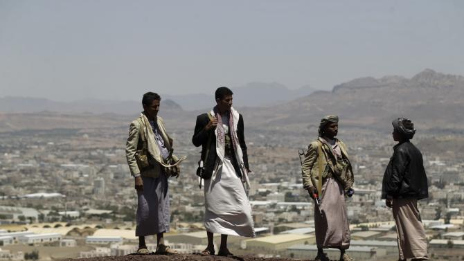 Shi'ite Houthi rebels stand on a hill at the army's First Armoured Division, after they took it over, in Sanaa