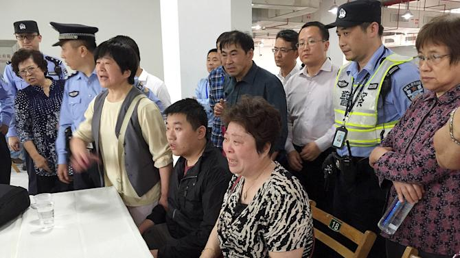 Relatives of passengers of the sunken cruise ship talk to government officers at an arranged meeting point in Shanghai