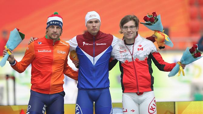 Russia's Pavel Kulizhnikov celebrates winning on the podium with Netherlands' Michel Mulder, second place, and Canada's Laurent Dubreuil, third place, after the men's ISU World Speed Skating Sprint Championship 500 meter event in Astana, Kazakhstan, Saturday, Feb. 28, 2015. (AP Photo/Alexei Filippov)