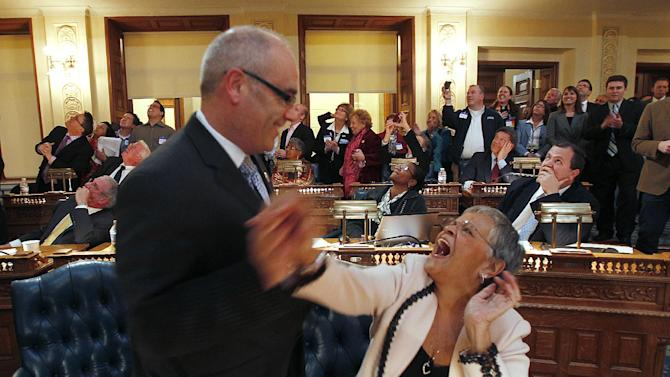 "FILe - In this Feb. 16, 2012, file photo, Assemblyman Reed Gusciora D-Trenton, left, and Assemblywoman Bonnie Watson Coleman D-Mercer, congratulate each other as the bill sponsored by Rep. Gusciora legalizing same-sex marriages, passes and is the final Legislative approval for Marriage Equality at the State House in Trenton, N.J. The 42-33 vote sends the bill to Gov. Chris Christie. The Republican governor who opposes gay marriage had promised ""very swift action"" if the bill reached his desk. Christie and most Republican lawmakers want gay marriage put to a popular vote. Democrats say gay marriage is a civil right protected by the Constitution and should not be subject to referendum. The country that President Barack Obama and Mitt Romney are vying to lead for the next four years is not quite the same as the one four years ago, not nearly the same as the one further back in time. On May 17, 2004, dozens of same-sex couples in Massachusetts took vows to become ""partners for life"" as the state became the first to recognize gay marriage despite the opposition of Romney, then governor. It has since become legal as well in Connecticut, Iowa, New Hampshire, Vermont, New York and the District of Columbia. Thirty-one states have passed measures aimed at banning gay marriage. (AP Photo/Rich Schultz)"