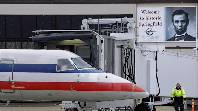 In this March 12, 2013 photo, a baggage handler walks by an American Eagle jet after it pulled up to a gate on arrival at the Abraham Lincoln Capital Airport in Springfield, Ill. The airport is one of nearly 240 small airports around the country that will likely shut down their air traffic control towers under federal budget cuts, stripping away a layer of safety during takeoffs and landings and leaving many pilots to manage the most critical stages of flight on their own. (AP Photo/Seth Perlman)