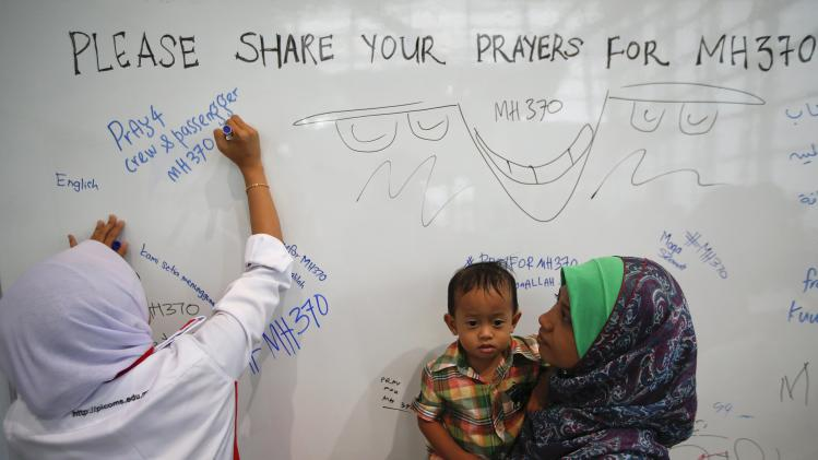 A woman leaves a message of support and hope for the passengers of the missing Malaysia Airlines flight MH370 at the Kuala Lumpur International Airport