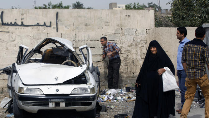 People inspect a damaged car at the scene of a car bomb attack in Zayona neighborhood of eastern Baghdad, Iraq, Wednesday, March 20, 2013. Iraqi officials say a car bomb in eastern Baghdad has killed and wounded a few people on the 10th anniversary of the US-led invasion, the day after a series of well-coordinated attacks left scores dead. (AP Photo/ Hadi Mizban)