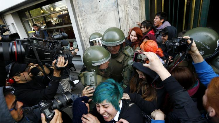 Riot policemen try to detain students after they occupied the Education Ministry building in downtown Santiago