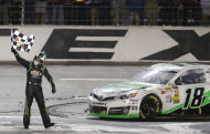 Sprint Cup Series's Kyle Busch (18) celebrates after winning the NASCAR Sprint Cup series NRA 500 auto race at Texas Motor Speedway Saturday, April 13, 2013, in Fort Worth, Texas. (AP Photo/Tony Gutierrez)
