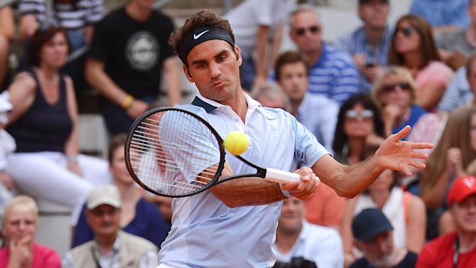 In this picture made available Thursday July 18, 2013 Switzerland's Roger Federer returns a ball during his match against German Daniel Brands at the German Open tennis tournament in Hamburg Wednesday July 17, 2013. (AP Photo/dpa,Axel Heimken)