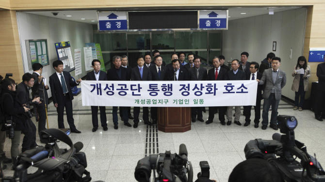 """South Korean small business owners who run factories in the sprawling complex in North Korea's border city of Kaesong, hold a press conference to demand that the North Korea to normalize the border crossings in front of the gateways to North Korea at the customs, immigration and quarantine office in Paju, South Korea, near the border village of Panmunjom, Thursday, April 4, 2013. North Korea on Wednesday barred South Korean workers from entering a jointly run factory park just over the heavily armed border in the North, officials in Seoul said, a day after Pyongyang announced it would restart its long-shuttered plutonium reactor and increase production of nuclear weapons material. The banner reads """" Normalize the border crossings. """" (AP Photo/Ahn Young-joon)"""
