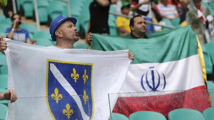 Fans of Bosnia, left, and Iran, right hold flags in support of their teams before the group F World Cup soccer match between Bosnia and Iran at the Arena Fonte Nova in Salvador, Brazil, Wednesday, June 25, 2014. (AP Photo/Marcio Jose Sanchez)