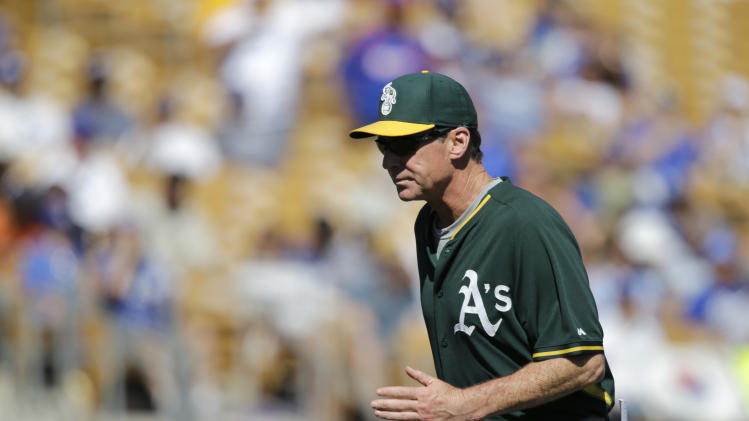 Oakland Athletics manager Bob Melvin returns to the dugout after a pitching change in a spring exhibition baseball game against the Los Angeles Dodgers Monday, March 10, 2014, in Glendale, Ariz. (AP Photo/Mark Duncan)