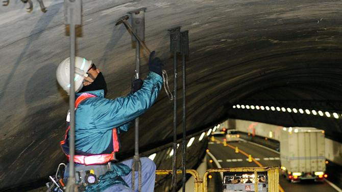 A worker inspects the structure inside the 1.65-kilometer (1-mile) Tsuburano Tunnel on the Tomei Expressway in Yamakitamachi, Kanagawa Prefecture, eastern Japan, Monday, Dec. 3, 2012. Concrete ceiling panels fell onto moving vehicles deep inside a tunnel on another expressway in Japan Sunday, and authorities confirmed nine deaths before suspending rescue work Monday while the roof was being reinforced to prevent more collapses. (AP Photo/Kyodo News) JAPAN OUT, MANDATORY CREDIT, NO LICENSING IN CHINA, FRANCE, HONG KONG, JAPAN AND SOUTH KOREA