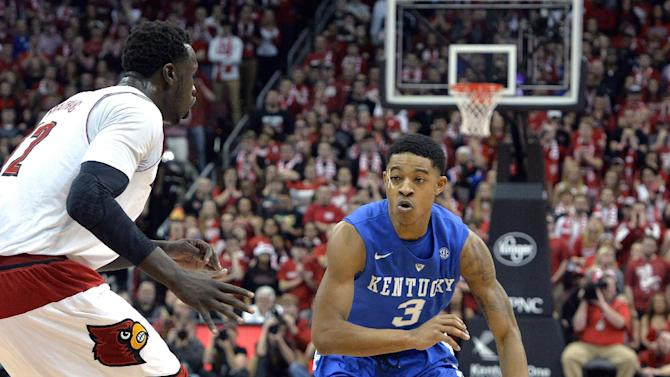 Kentucky's Tyler Ulis, right, drives against Louisville's Mangok Mathiang during the first half of an NCAA college basketball game Saturday Dec. 27, 2014, in Louisville, Ky. Kentucky won 58-50 (AP Photo/Timothy D. Easley)