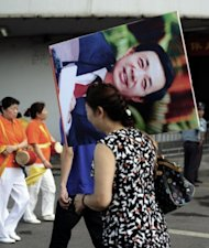"File photo shows a Chinese woman in Chongqing carrying a protrait of Bo Xilai after a ""red"" culture session, where workers gather to sing revolutionary songs. Bo, until recently a rising political star, was known in for busting gangs and reviving Maoist ideals in Chongqing"