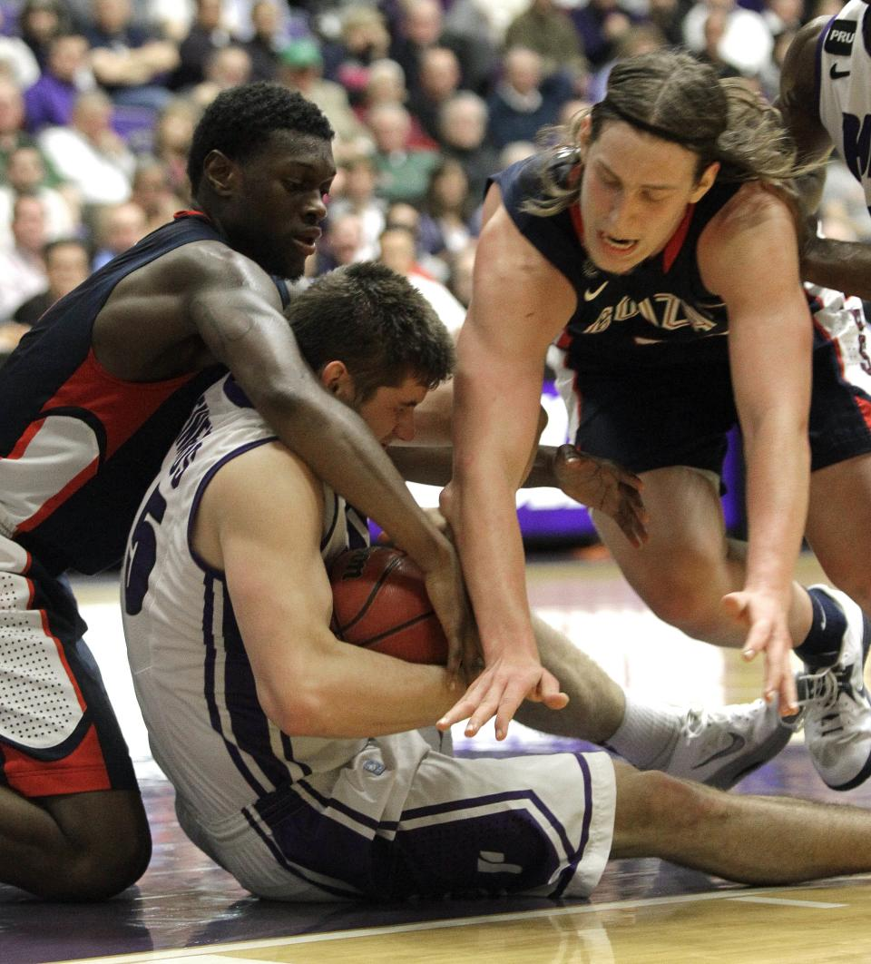 Gonzaga's Kelly Olynyk, right, and Gary Bell, Jr., left, battle for the ball with Portland guard Oskars Reinfelds during the second half of an NCAA college basketball game in Portland, Ore., Thursday, Jan. 17, 2013.  Gonzaga won 71-49.(AP Photo/Don Ryan)