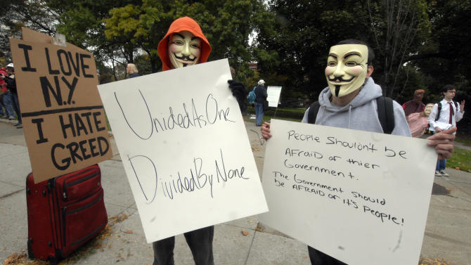 "In this Friday, Oct. 21, 2011 photo, Papi Chulo, left, and Brian Xaivier, both of Ravena, N.Y., wear Guy Fawkes masks while supporting the Occupy Wall Street movement in Albany, N.Y. From New York to San Francisco to London, some of the demonstrators decrying a variety of society's ills are sporting stylized masks loosely modeled on a 17th-century English terrorist, whether they know it or not. The masks come from ""V for Vendetta,"" a comic-based movie whose violent, anarchist antihero fashions himself as a modern Guy Fawkes, the Catholic insurrectionist executed four centuries ago for trying to blow up Parliament. (AP Photo/Hans Pennink)"