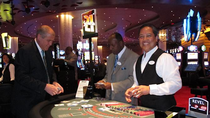 Dealer Elbert Taclan, right, prepares a card game moments after the $2.4 billion Revel casino resort opened in Atlantic City, N.J. on April 2, 2012. John Koryto, left, was watching him prepare for the first customers to arrive at the table. Three major unions including the Teamsters and the United Auto Workers announced a drive on April 30, 2012 to fully unionize the new casino, including dealers. (AP Photo/Wayne Parry)